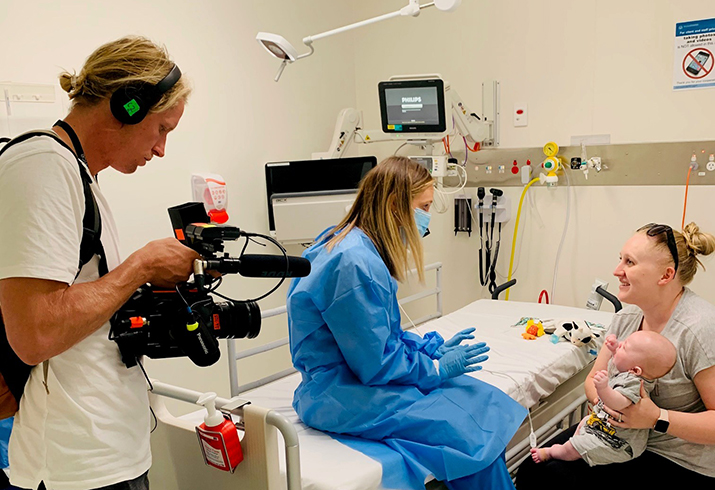 Documentary videographer filming a nurse, mother and baby in PCH ED