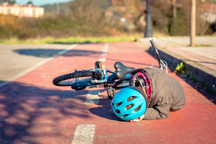 Child with bike helmet lying on the ground following a bike accident